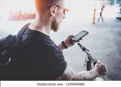 Bearded muscular tattooed hipster in sunglasses using smartphone after riding by electric scooter in the city. Innovative transport