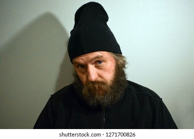 A bearded and mustache man in a black hat looks stern. A man of European appearance 50 years old looks with reproach and disbelief.