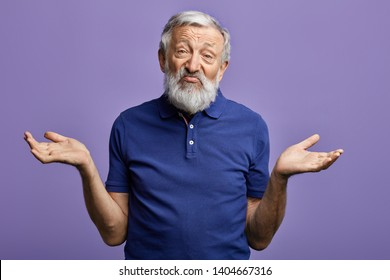 bearded old man expresses clueless with raised arms looking at the camera.isolated blue background. it doesn't bother me. it doesn't care me.I don't know. I don't have an idea. studio shot.