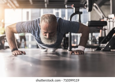 Bearded old pensioner male is having workout in gym