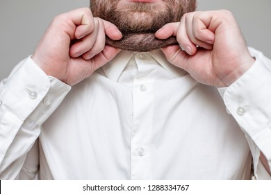 bearded person pinching himself on his double chin, wearing a white shirt on a gray background