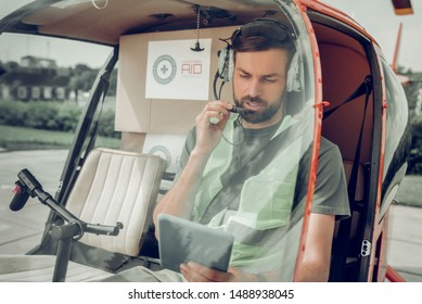 Bearded pilot. Handsome bearded pilot working for humanitarian company sitting in little helicopter