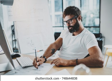 Bearded professional architect wearing eye glasses working at modern loft studio-office with desktop computer.Blurred background. Horizontal