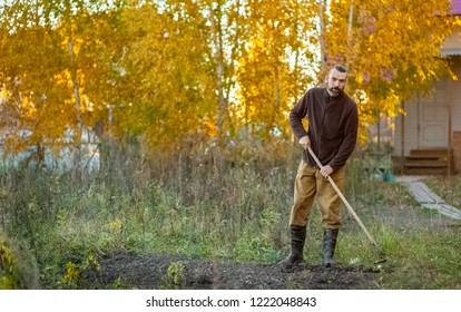 a bearded Russian man with a hoe in his hands in the autumn prepares beds for planting tubers