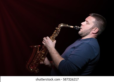 Bearded saxophonist playing inspired on saxophone isolated on a black background