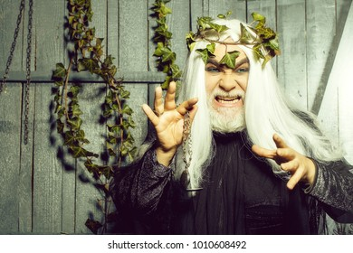 Bearded senior angry strange man wizard in long white wig vine crown as Zeus god with medallion on chain indoor on wooden background