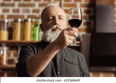 Bearded senior man looking at wine glass with red wine