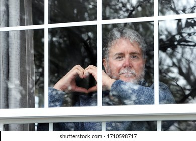 Bearded senior man making heart symbol with hands at the window during quarantine, focus on hands and eyes