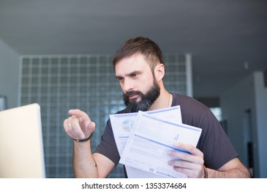 Bearded serious concentrated man working at laptop and sitting at the table while looking at the papers and holding his head with hand.
