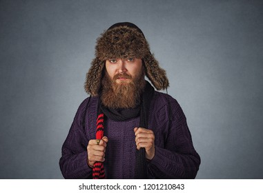 Bearded serious male man in fluffy Russian fur hat cap dressed in a pullover sweater holding red scarf posing Isolated on gray grey studio wall Background. Neutral face expression.