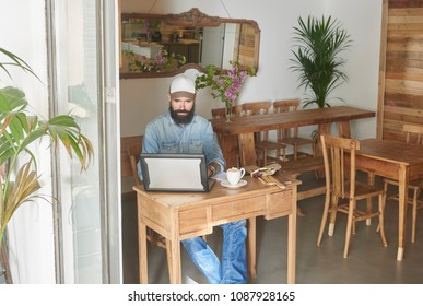 Bearded serious man browsing laptop sitting alone at small table with morning meal.