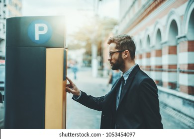 Bearded serious man entrepreneur in eyeglasses and a formal suit is using parking pay station terminal; handsome businessman in glasses and with the beard paying his parking time via automatic kiosk