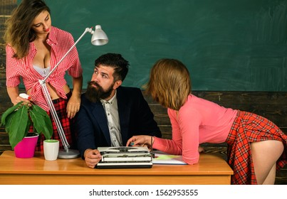 Bearded sexology teacher looks at two sexy female students. Erotic education and sex Symbols on chalkboard. Sex education. Anatomy lesson and sex education in high school. Let's Talk Sex.