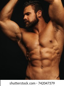 Bearded shirtless fitness man looking to the left