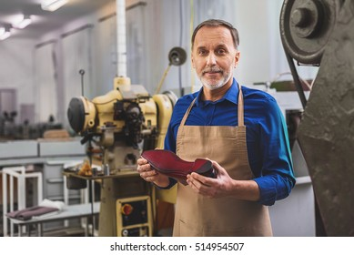bearded shoemaker holding footwear and smiling