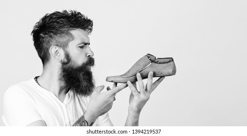 Bearded shoemaker on white background, copy space. Bearded man holding last shoe. Serious young cobbler sets up business. Shoemaker holding wooden footwear.