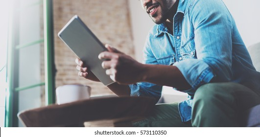 Bearded smiling African man using tablet for video conversation while relaxing on sofa in modern office.Concept of young business people working at home.Blurred background.Horizontal wide