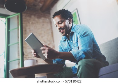 Bearded smiling African man using tablet for video conversation while relaxing on sofa in modern office.Concept of young business people working at home.Blurred background.Selective focus