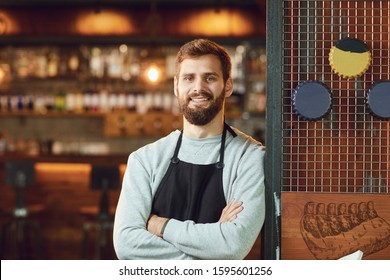 Bearded smiling barman waiter standing on the background of a bar.