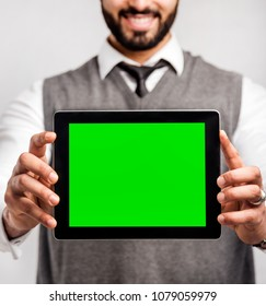 Bearded smiling businessman holds tablet computer with green screen on isolated white background
