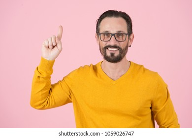 Bearded smiling man in glasses pointing up by finger on pink background. Happy man with finger up. Wise Man in glasses notices up with finger. Clever guy in orange on pink background. Happy and clever