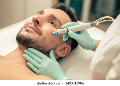 Bearded smiling man lying on the pillow and hands of cosmetologist in rubber gloves holding a modern tool for skin nourishment