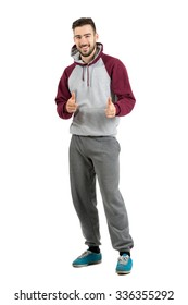 Bearded smiling young man in casual sportswear pointing finger gun hand gesture at camera. Full body length portrait isolated over white studio background.