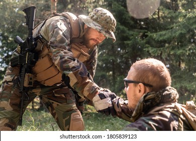 Bearded soldier in hat and vest giving hand to wounded military friend while picking him up off ground in forest