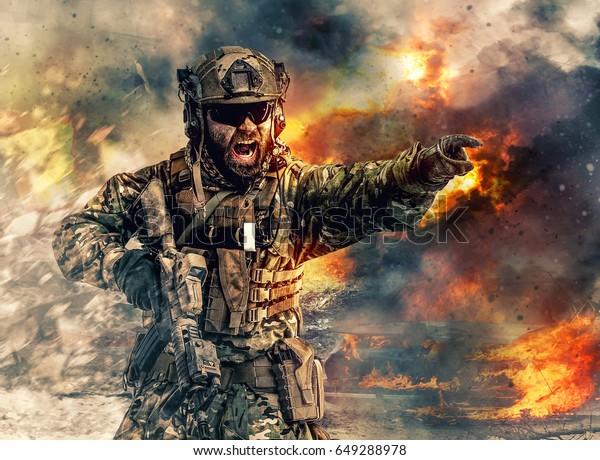Soldado de las fuerzas especiales en acción apuntando al objetivo y dando dirección al ataque. Ruinas quemadas, explosiones intensas, disparos y humo nublado en segundo plano