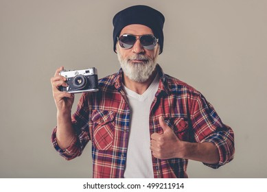 Bearded stylish mature man in casual shirt, black cap and sun glasses is holding a photo camera, showing Ok sign and smiling, on a gray background