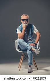 Bearded stylish mature man in jeans wear and sun glasses is looking at camera leaning on his hand while sitting on a chair on a gray background