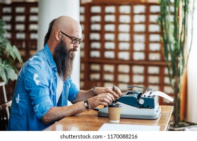 Bearded stylish writer typing on typewriter. Modern writer in glasses working on new book in library