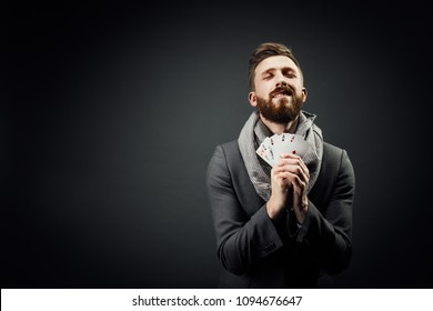 bearded stylish young handsome man holding playing cards in his hands for the casino and looking up emotionally, blessing god. dark studio background
