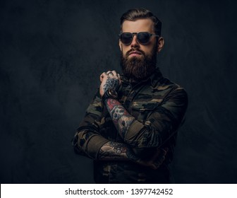 Bearded tattooed guy in military shirt and sunglasses posing with thoughtful look. Studio photo against a dark wall