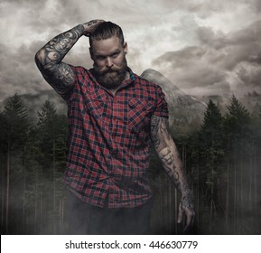 Bearded tattooed male in a red shirt over dark forest and cloudy sky.