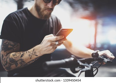 Bearded tattooed man in sunglasses using mobile phone for send text message after riding by electric scooter in the city