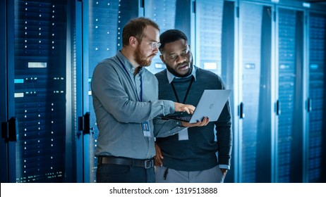 Bearded IT Technician in Glasses with Laptop Computer and Black Male Engineer Colleague are Using Laptop in Data Center while Working Next to Server Racks Running Diagnostics or Doing Maintenance Work