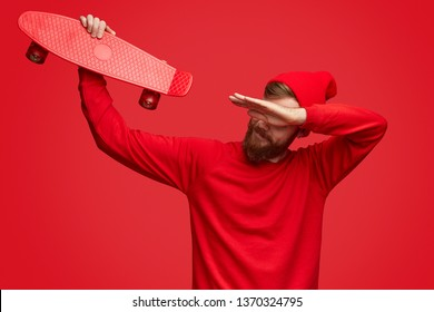 Bearded teenager in trendy red outfit holding modern skateboard and performing dab move while dancing against bright background