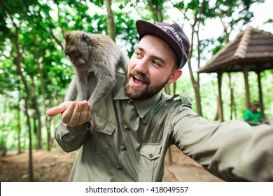 Bearded tourist and blogger takes selfie portrait with wild monkey in Monkey Forest, Ubud, Bali, Indonesia