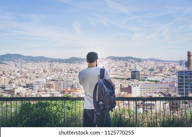 Bearded Tourist Man with backpack enjoy beautiful panoramic view of modern european city.Traveler man looking on a big city, travel and active lifestyle concept