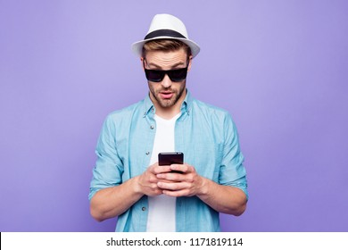 Bearded trendy stylish shocked guy wearing casual shirt, black sun glasses and sunhat, buying online goods on mobile online app store, over bright vivid violet purple background
