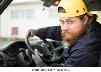 The bearded truck driver in overalls and a cap is going to go to perform the task. He looks into the open cab window at the viewer.