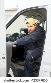 The bearded truck driver in overalls and a cap closes the car door. He's going to go to perform the task.