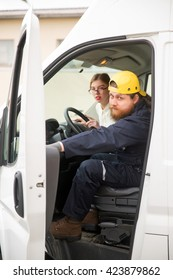 The bearded truck driver in overalls and a cap closes the car door. He's going to go to perform the task. A girl is the passenger of the truck. She looks out over the driver's shoulder.