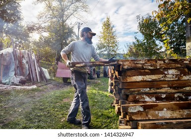 Bearded worker, carpenter, yard worker manipulates wood pillars. The young lumberman and the wood pile, treated against rotting, by carbonization. Old traditions, rudimentary preservation techniques.