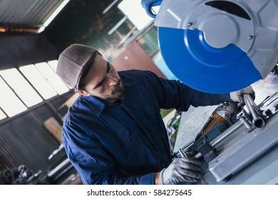 Bearded worker cutting metal bar with circular saw