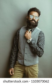 Bearded young businessman posing with sunglasses