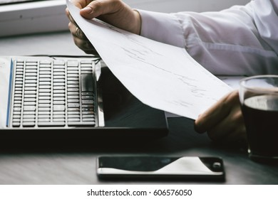 Bearded young businessman working at modern office.Man wearing white shirt and making notes on the documents.Panoramic windows background. Horizontal, film effect.Blurred