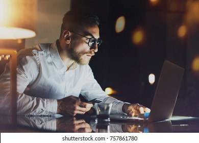 Bearded young businessman working at night office.Man using contemporary mobile notebook.Horizontal.Blurred background. Flares and reflections effect. Cropped