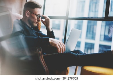 Bearded young businessman working on modern loft office. Man sitting in vintage chair. Using contemporary notebook, panoramic windows background. Horizontal, film effect.